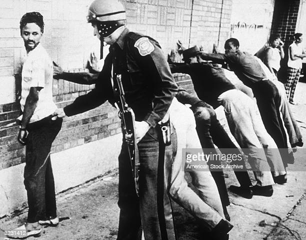 Police frisk an AfricanAmerican man as other suspects lean against wall on 12th Street where looting was in progress during the Detroit riots Michigan