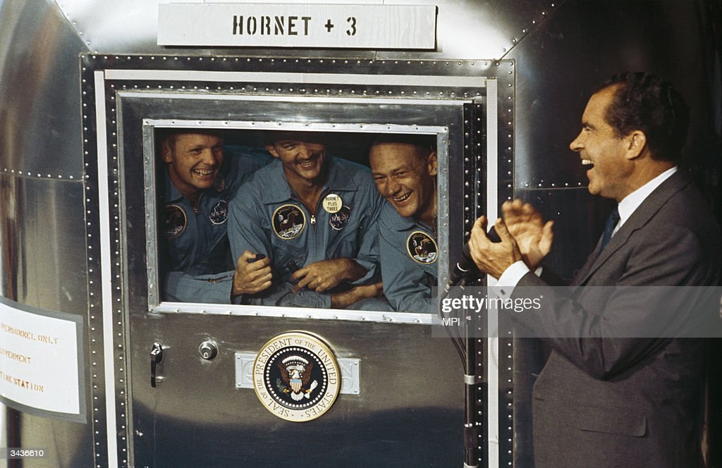 From left to right, Neil Armstrong, Michael Collins and Edwin 'Buzz' Aldrin Jnr, the crew of the historic Apollo 11 moon landing mission are subjected to a period of quarantine upon their return to earth. Through the window of their Mobile Quarantine Facility, they hold a conversation with President Richard Nixon (1913 - 1994).