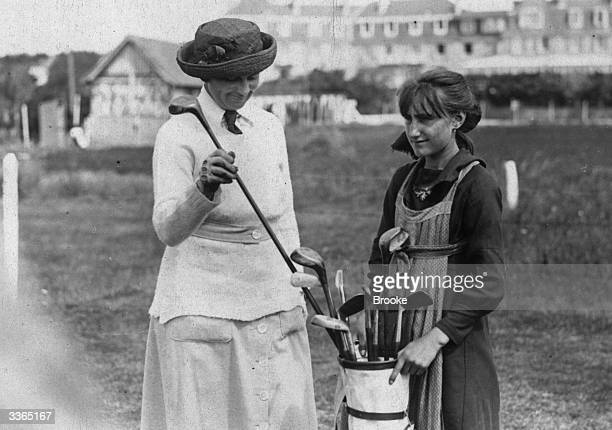A caddy holds the bag as Mrs Vanderbeck choosing her club at the French Ladies Golf Championship at Le Touquet