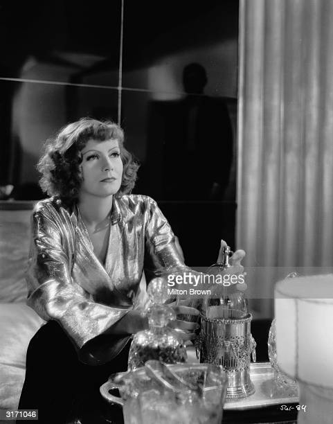 Greta Garbo pours herself a drink in a scene from 'Susan Lenox Her Fall And Rise' directed by Robert Z Leonard Behind her stands a silhouetted Clark...