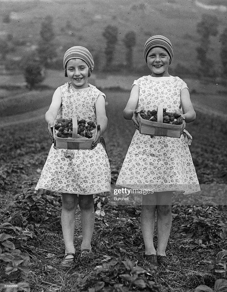 Two girls, who have been helping with the strawberry harvest, holding up their full punnets at a strawberry field in Cheddar, Somerset.