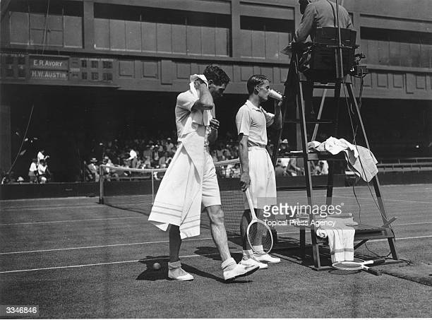 Bunny Austin of Great Britain takes a refreshing drink at the umpire's chair after his defeat of E R Avory at the Wimbledon Lawn Tennis Championships