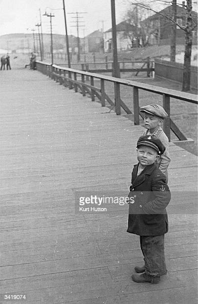 A child wearing a miniature sailor's costume whilst he and with his friend watch a Canadian Pacific Railway train which has paused at his station on...