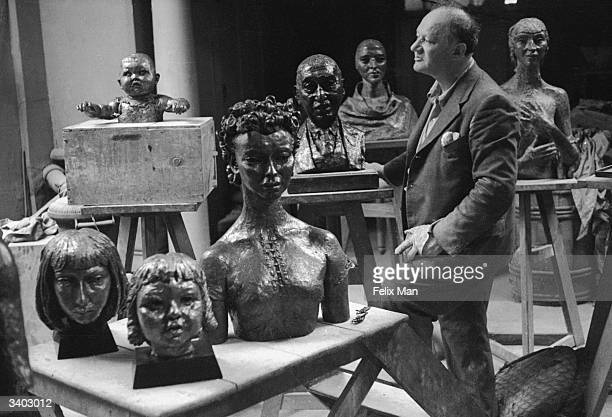 USborn British sculptor Sir Jacob Epstein standing amongst pieces of his sculpture Original Publication Picture Post Epstein's Adam pub 1939