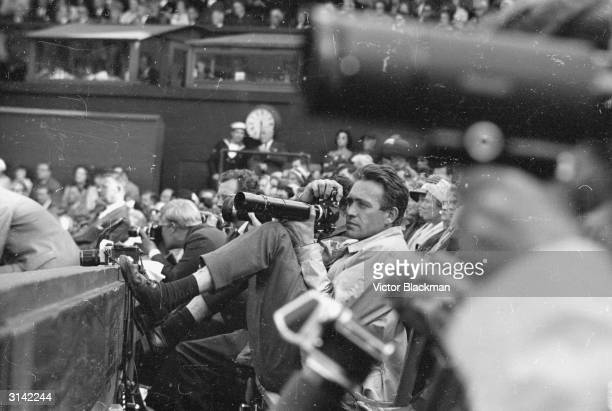 A photographer leans back to get the perfect shot in the press box at Wimbledon