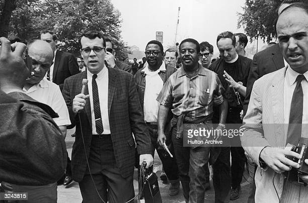 American clergyman and civil rights leader Dr Ralph Abernathy centre walks with supporters while members of the media surround them during a Poor...