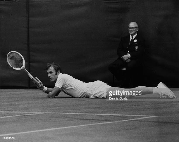 John Newcombe of Australia lands up flat on the ground during a men's singles match at Wimbledon to the amusement of a linesman