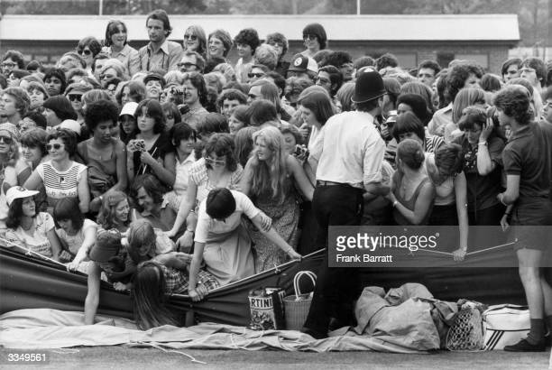 A policeman tries to control the crowd as girls spill over a collapsed barrier in their attempt to catch a glimpse of their heroes during a knockup...