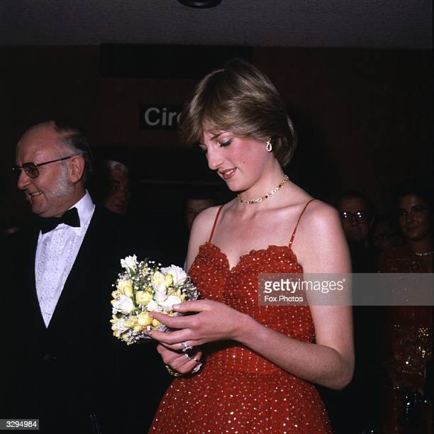 Lady Diana Spencer , examines her bouquet at the premiere of the film 'For Your Eyes Only', at the Odeon, Leicester Square.