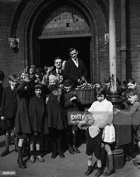 Hot cross buns are distributed to the children outside the Memorial Hall Bethnal Green London after an Easter Service
