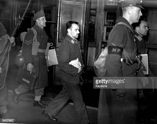 German airman, a prisoner of war, being marched between guards and military police at a London railway station.