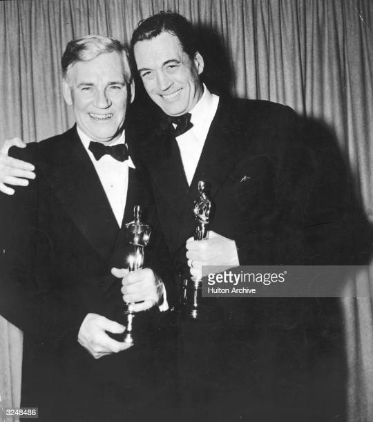 American actor Walter Huston and his son director and screenwriter John Huston hold their Oscar trophies for the film 'Treasure of the Sierra Madre'...