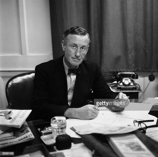 Ian Fleming British author and creator of James Bond at his desk in his study