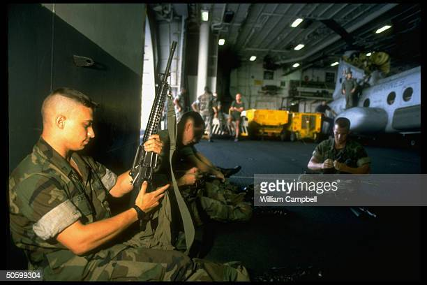 24th Marine Expeditionary Unit marines cleaning M16 rifles in hangar abd USS Inchon re possible USled invasion of Haiti to restore ousted Pres