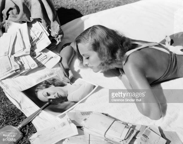 American actress Joan Crawford answers a sack of fan mail and autographs photographs to enclose with the replies. A mirror lies on the grass nearby,...