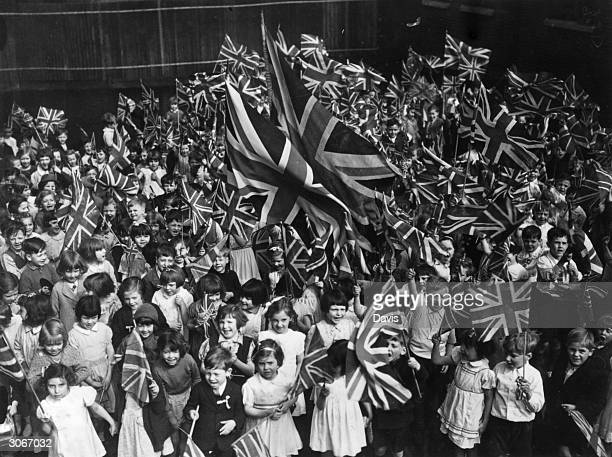 A crowd of cheering children wave Union Jacks as they celebrate Empire day at the Hugh Myddleton LCC Schools Clerkenwell London