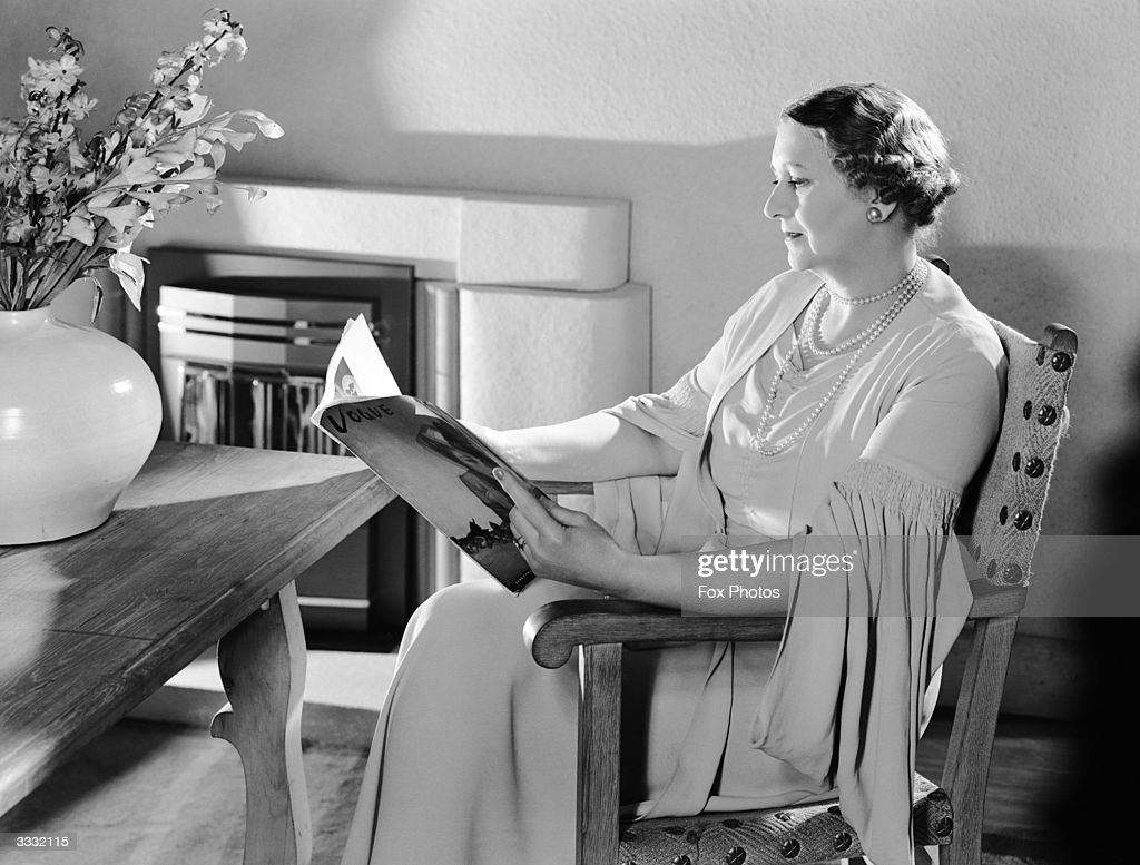 Sitting by an electric fire an elegantly dressed middle aged woman, Adele Benson, reads a magazine.
