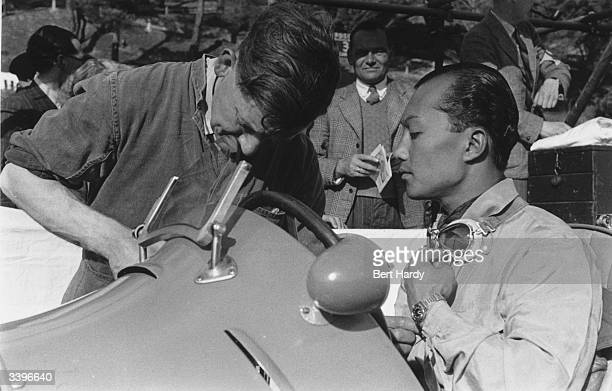 Prince Birabongse of Siam sitting in the cockpit of his racing car whilst a mechanic makes final adjustments to it before a race in Jersey Original...