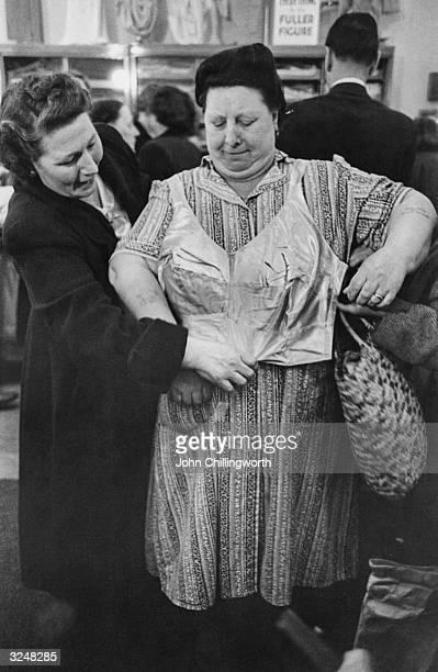 A generouslybuilt lady tries on a bra at Evans the Outsize Shop in south London Original Publication Picture Post 5868 Outsize Sale pub 1952