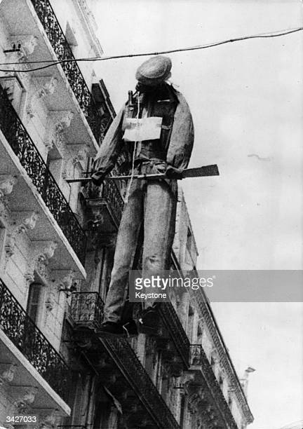 A human effigy holding a gun hangs from telephone wires across a main street in Oran A placard hanging from its neck reads 'Force Locale'