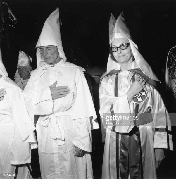 Members wearing the robes and hoods of American white supremacist organisation Ku Klux Klan with their hands on their hearts at a klan meeting in...