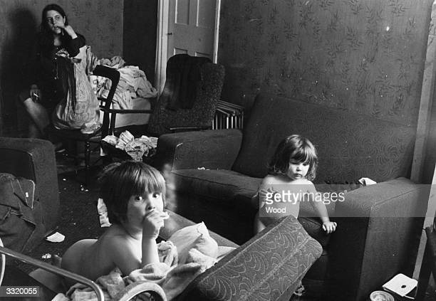 A couple of nude toddlers and their mother in their untidy sitting room