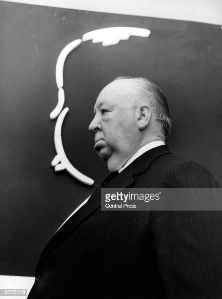 Alfred Hitchcock in front of a caricature of his profile at a press reception in London for his new film 'Frenzy'