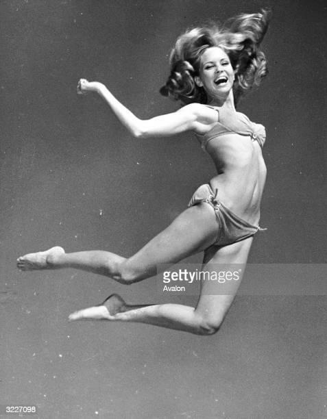 Fashion model Susi Carroll jumps into the air wearing a skimpy bikini at Miami Beach, Florida.