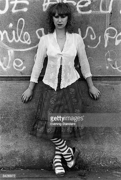 British actress Helen Mirren leaning against a graffiticovered wall