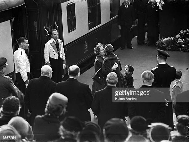 Queen Elizabeth II embracing Queen Elizabeth The Queen Mother as Princess Anne looks on at Waterloo Station London on the latter's return from a tour...