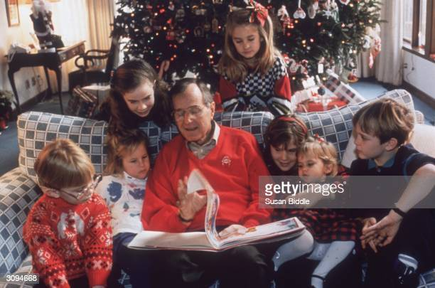 American statesman George Bush the 41st President of the United States reading a Christmas story to his grandchildren on Christmas Eve at the White...