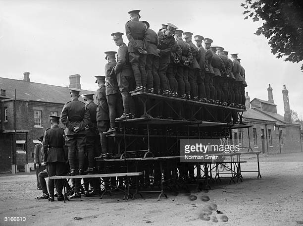 The 24th Field Battery of the Royal Artillery balance on a framework of planks in Aldershot for an official photograph. But one soldier seems a...