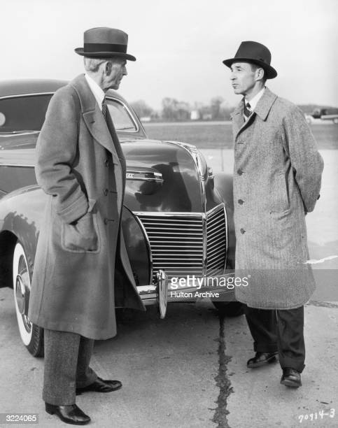 Full-length image of American inventor and industrialist Henry Ford and his son, auto executive Edsel Ford , standing in front of the 1939 Ford...