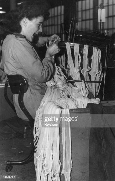 A worker in a Liverpool nylon stocking factory operates a 'linking' machine In postwar Britain there is a shortage of operators of this type of...