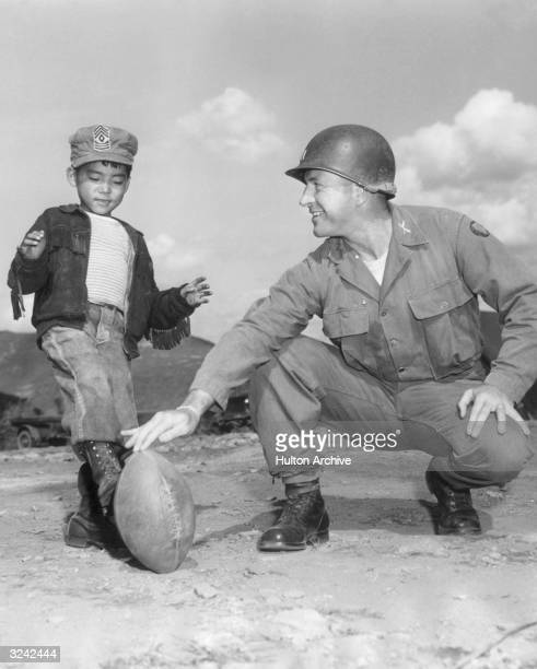 US Army Captain Edward Buckley a former football player for the Green Bay Packers crouches down to hold a football as Al a fiveyearold Korean orphan...