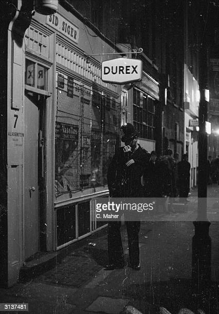 A policeman outside the Archer Room Club in Archer Street Soho London where a hostess was recently shot A shop sign advertising Durex condoms hangs...