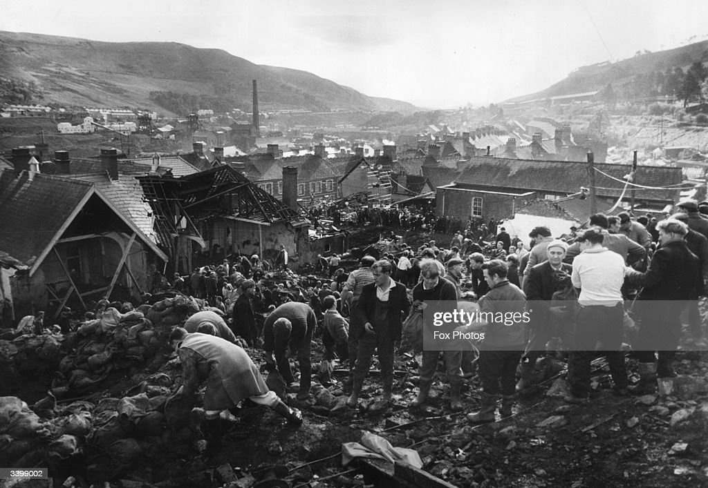 Helpers filling sandbags on the tip above the shattered Pantglas Junior School to divert a spring and avert the risk of further landslides at Aberfan, South Wales.
