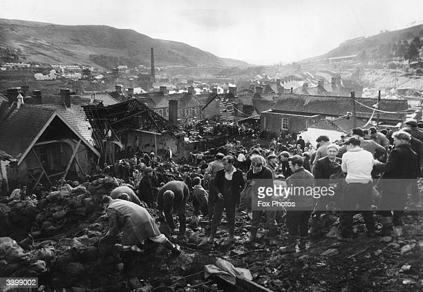 Helpers filling sandbags on the tip above the shattered Pantglas Junior School to divert a spring and avert the risk of further landslides at Aberfan...