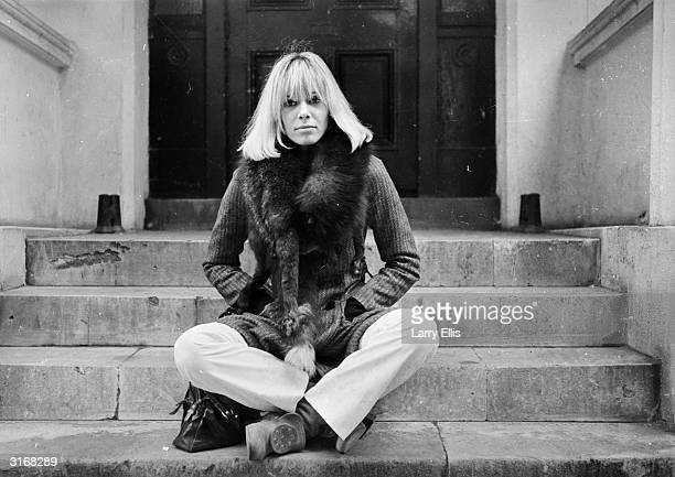 Italianborn German actress Anita Pallenberg sits crosslegged on a flight of stone steps with her hands in her pockets