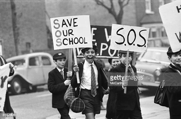Pupils of the Walpole Grammar School in Ealing stage a protest march to the town hall carrying placards with the slogan 'SOS Save Our School' They...