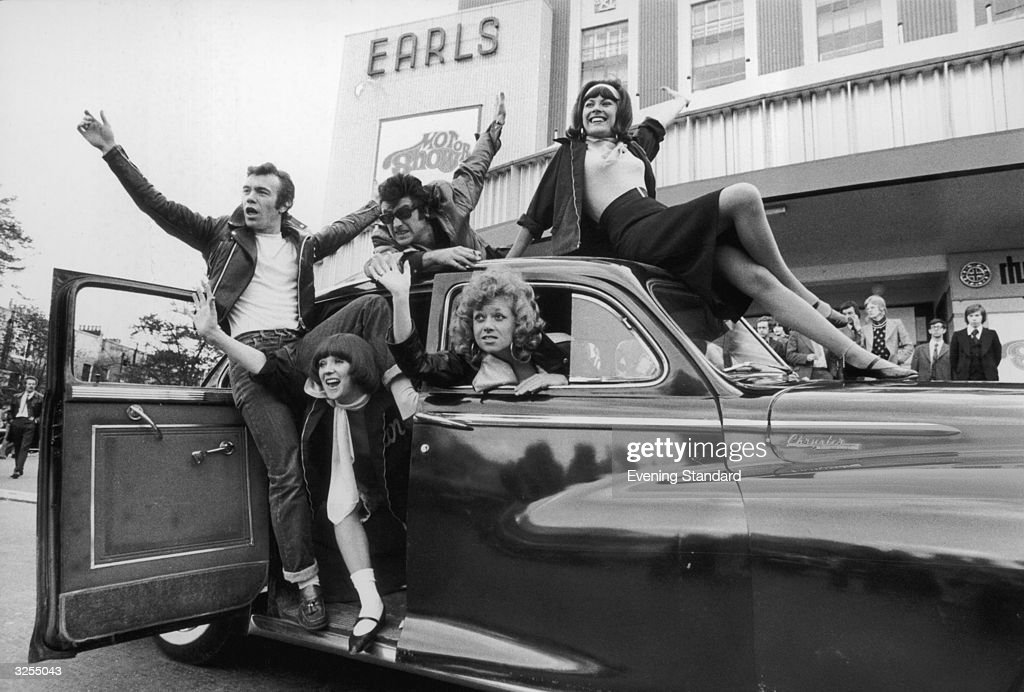 The cast of the show 'Grease', a new 1950's rock and roll musical, arrive at Earls Court London for the 1973 Motor Show driving a Chrysler Windsor circa 1950.
