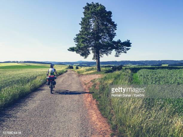 24th of june 2019. woman long distance biker with camping bags is riding by road through fields - czech republic stock pictures, royalty-free photos & images