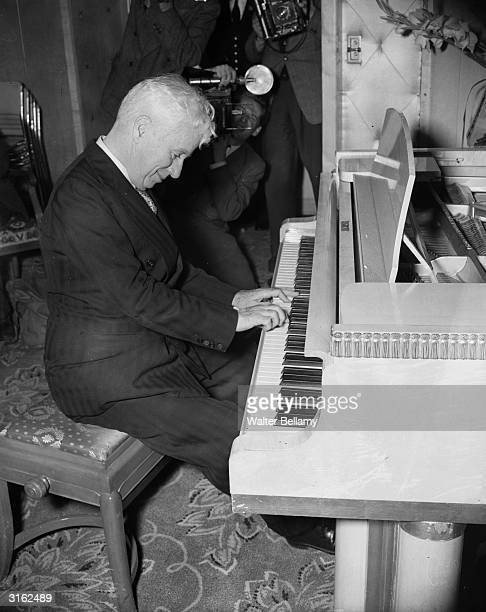Britishborn actor director and musician Charles Chaplin playing the piano