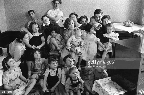 Charles and Elizabeth Hudson watching television with some of their twenty children and six grandchildren in their eightroom Victorian house in...