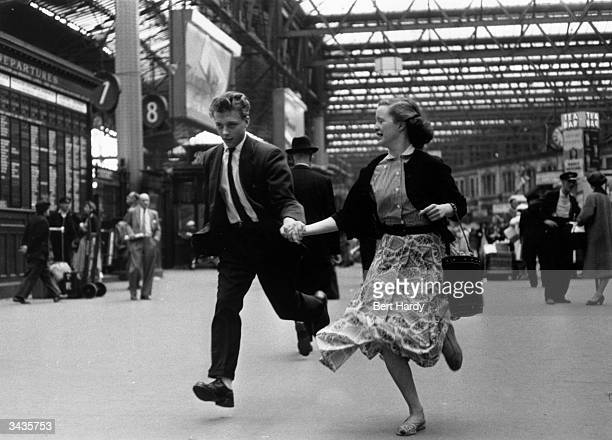 Two young employees of the Hulton press running through Waterloo train station London Original Publication Picture Post 8002 Leave Youth Alone pub...