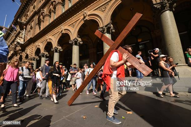 24yearold student Alec Green depicting himself as Jesus Christ carries a cross in a reenactment from the Bible on Good Friday in Sydney on March 30...