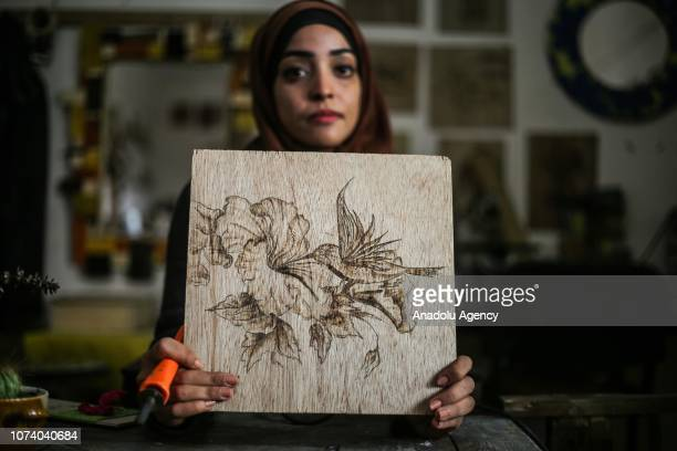24yearold Vela Ebu Aysh poses with her woodburning art work at her studio in Rafah Gaza on December 10 2018 Ebu Aysh also teaches woodburning...