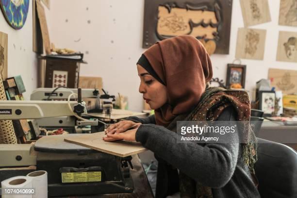 24yearold Vela Ebu Aysh works on woodburning art at her studio in Rafah Gaza on December 10 2018 Ebu Aysh also teaches woodburning techniques at an...