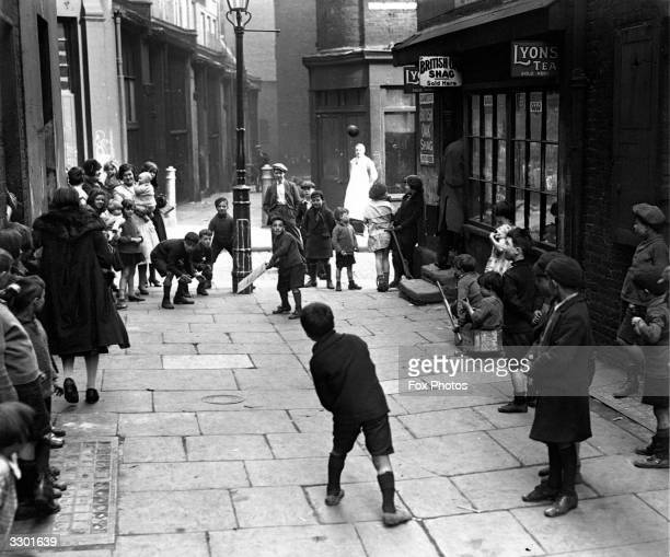 Children playing cricket in a London street with the wicket drawn on a lamppost