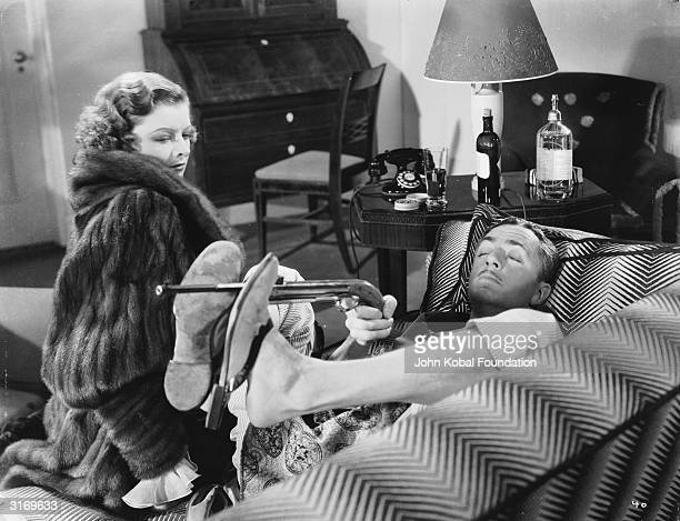Myrna Loy and William Powell play sleuthing couple Nick and Nora Charles in 'The Thin Man' directed by W S Van Dyke In this scene Nick practises his...